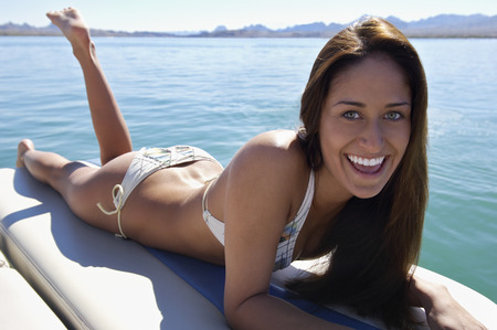 Young woman relaxing on boat, smiling, portrait Stock Photo - 3812206