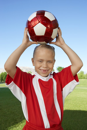 Girl (7-9 years) soccer player holding ball above head, portrait Stock Photo - 3812202