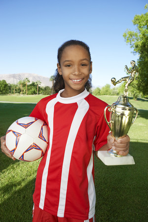 Girl (7-9 years) soccer player holding trophy and ball, portrait Stock Photo - 3812565