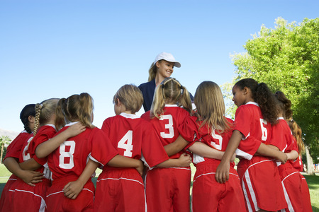 Group of children soccer players embracing standing in front of coach, back view Stock Photo - 3812540