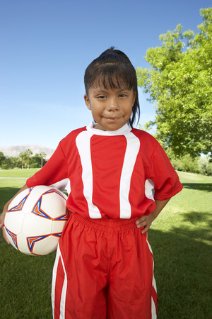 Girl (7-9 years) soccer player holding ball under arm, portrait Stock Photo - 3812518