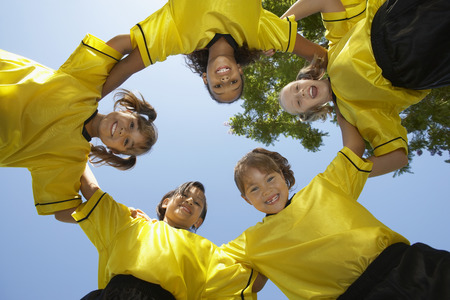 huddling: Five children soccer players (7-9 years) huddling, view from below, portrait LANG_EVOIMAGES