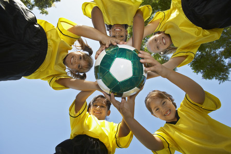 ниже: Five children (7-9 years) holding soccer ball, view from below, portrait