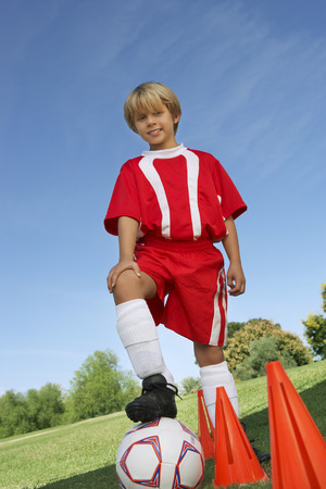 Boy (7-9 years) soccer player holding foot on ball, portrait Stock Photo - 3812160