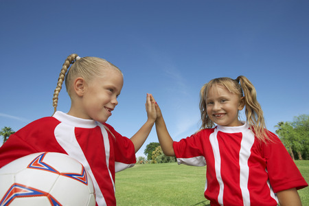 Two girl soccer players (7-9 years) doing 'high five' on soccer field Stock Photo - 3812340