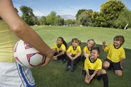 coach: Coach standing in front of group of girl soccer players (7-9 years) sitting on lawn, elevated view LANG_EVOIMAGES
