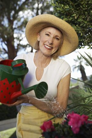 Woman watering flowers in garden Stock Photo - 3812471