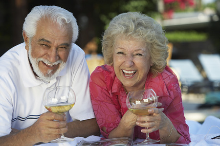 longevity: Portrait of senior couple relaxing in garden with wine and laughing