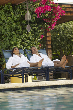 Couple in bathrobes relaxing by swimming pool Stock Photo - 3812563