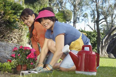 Two women planting flowers in garden Stock Photo - 3812650