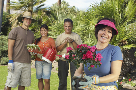Four people gardening, focus on woman with flower in foreground Stock Photo - 3812580