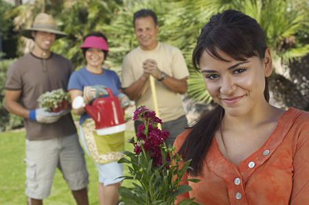 Four people gardening, focus on woman with flower in foreground Stock Photo - 3812554