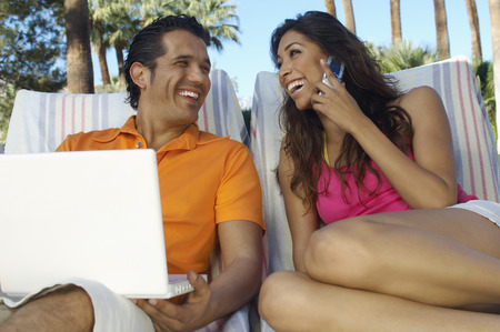 Couple with laptop and mobile phone relaxing in deckchairs Stock Photo - 3812308