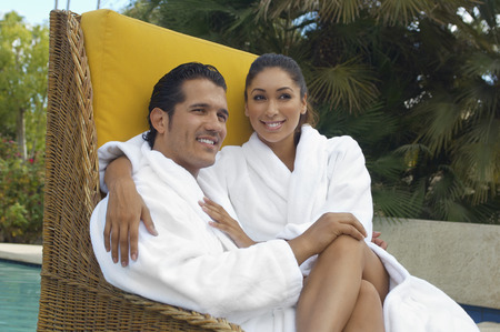 Couple in bathrobes relaxing in wicker chair by pool Stock Photo - 3812543