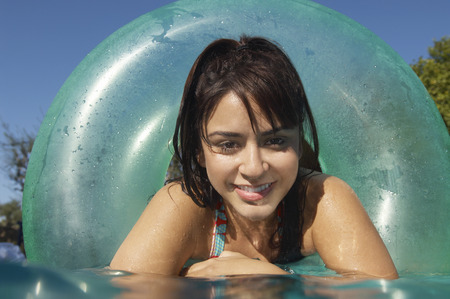 Young woman in inflatable ring in swimming pool, close-up Stock Photo - 3812545