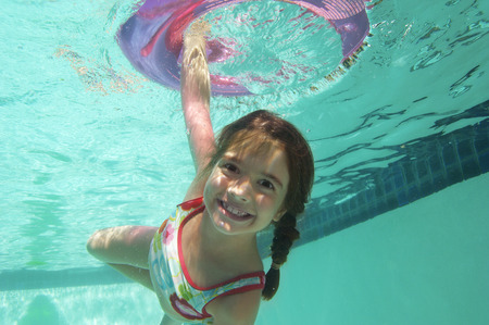 Girl holding inflatable raft underwater in swimming pool, portrait Stock Photo - 3812676