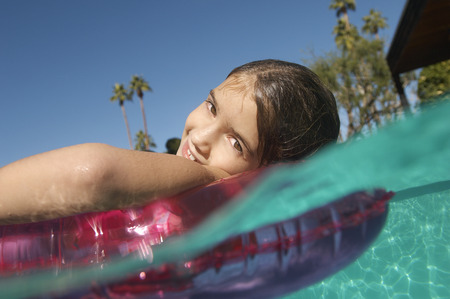 Girl floating in inflatable raft in swimming pool Stock Photo - 3812547