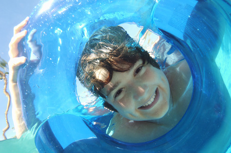 Boy looking through inflatable raft in swimming pool, underwater view