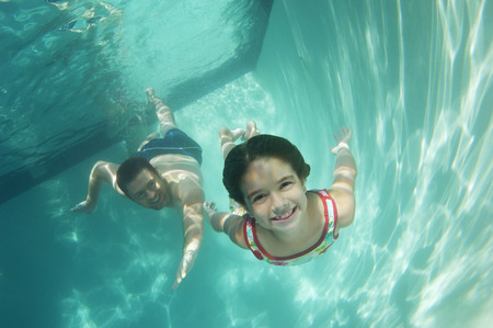 Father and daughter swimming, underwater view Фото со стока