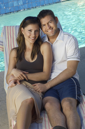 Couple in deck chair by swimming pool, portrait Stock Photo - 3812417
