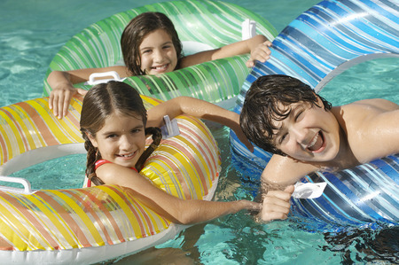 Three children in inflatable rafts in swimming pool, portrait Stock Photo - 3812674