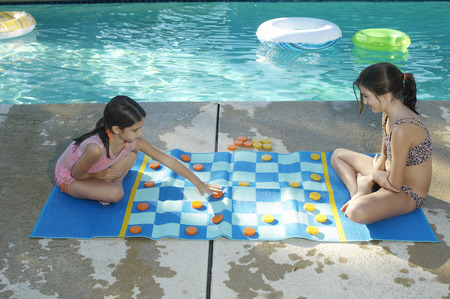 draughts: Two girls playing on large draughts board beside swimming pool