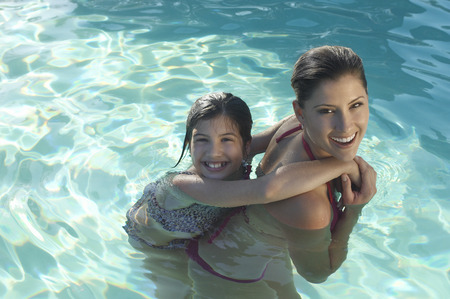 Mother giving daughter piggy back in swimming pool, portrait Stock Photo - 3812437