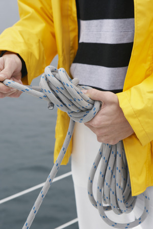 Young man tying rope on yacht, mid section Stock Photo - 3811165