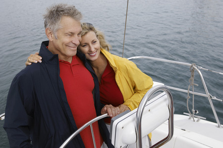 elevated view: Couple at helm of sailboat, smiling, elevated view