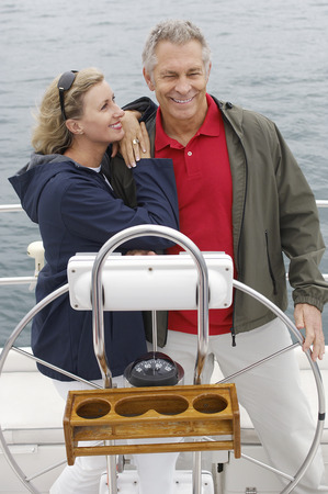 Couple at helm of sailboat, smiling Stock Photo - 3812497