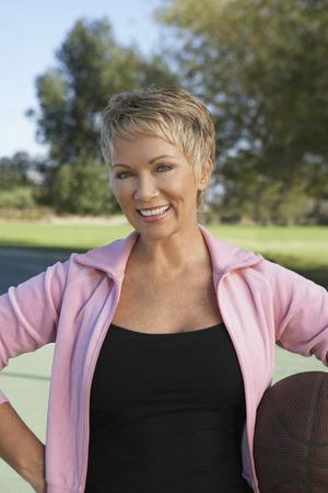 Senior woman holding basketball outdoors, portrait Stock Photo - 3812280