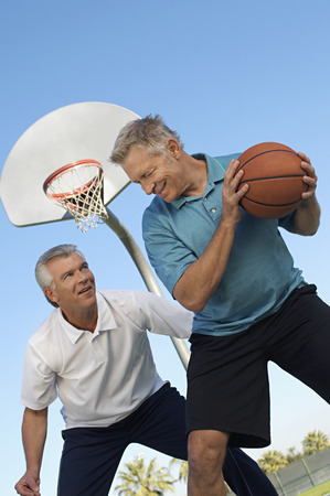 Senior men playing basketball on outdoor court Stock Photo