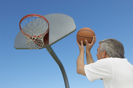 Senior man aiming basketball at hoop, outdoors Stock Photo - 3812510