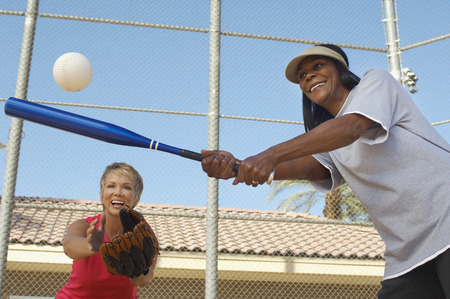 Senior woman hitting softball with other woman catching Stock Photo - 3812564