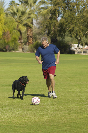 Senior man kicking soccer ball with dog in park Stock Photo - 3812668