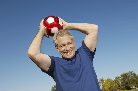 1 adult only: Senior man holding soccer ball over head, outdoors