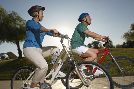 Senior couple cycling in park at dusk Stock Photo