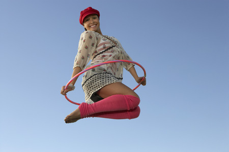 Portrait of woman jumping with Hula Hoop