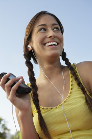 Young woman listening to mp3 player Stock Photo - 3811234