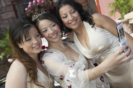 Bride taking self-portrait with two friends using mobile phone Stock Photo - 3812404