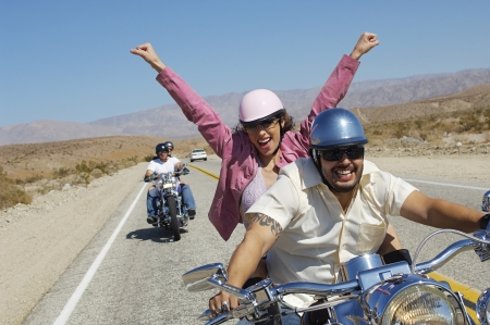 two people with others: Bikers riding on desert road