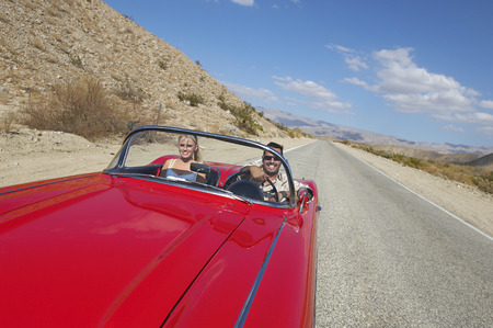 scenic drive: Couple in classic car on desert road LANG_EVOIMAGES