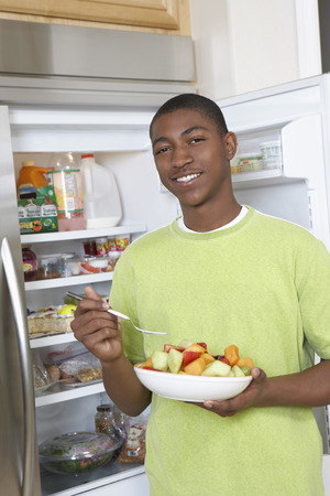 Young man eating salad by open fridge Stock Photo - 3811212