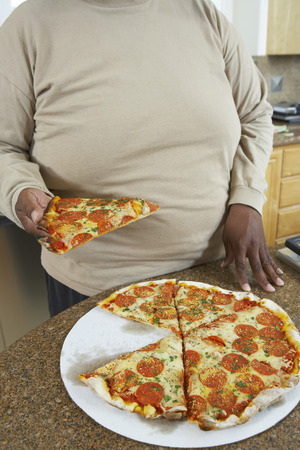 kitchen counter: Man taking slice of pizza from kitchen counter