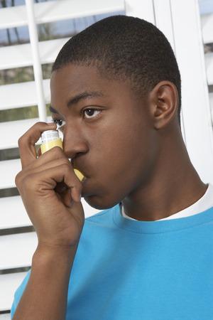 inhaler: Young man using asthma inhaler