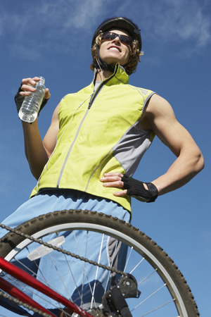 Male cyclist holding water bottle, outdoors Stock Photo - 3812210