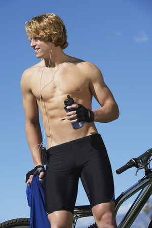 Male cyclist holding water bottle, outdoors Stock Photo - 3812218