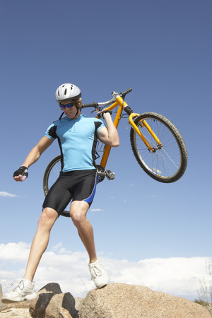 Young man carrying bicycle on rocks Stock Photo - 3811149