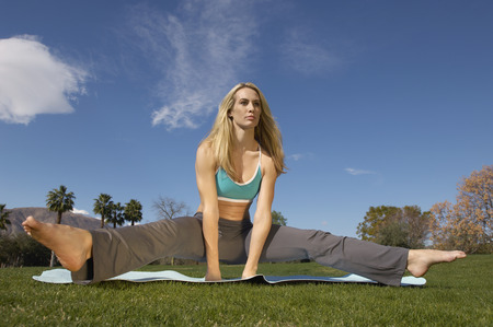 apart: Young woman performing yoga exercises in park