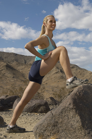 apart: Female jogger stretching in mountains